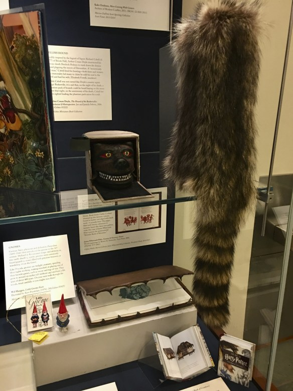 "Display case featuring a raccoon skin, a fierce hound's face (the biding for a book about Conan Doyle's Holmes story ""The Hound of the Baskervilles""), and a leather book edged with shark teeth."""