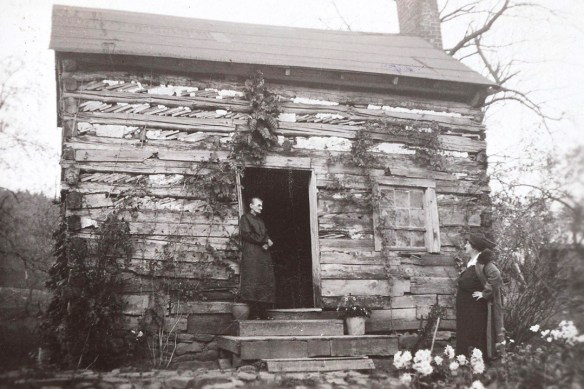 A B&W photo of a rustic log house. A woman, framed in the doorway, is speaking with another outside.