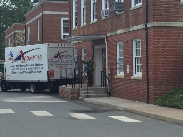 Moving van backed up to a rear door of the Astronomy building. Ricky Patterson, in back of the van, waves to the camera.