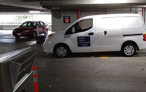 White van labeled Library Express On-Grounds is parked on Level 2 of a parking garage