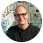 Photo of cartoonist Rob Rogers, smiling man wearing glasses in front of drawings pinned to a wall