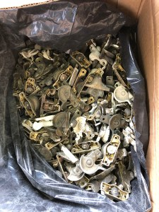 View from above of a box containing various types of window hardware.