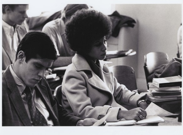 Black and white photo of woman in smart coat with afro, in classroom