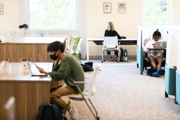 Students wearing face coverings at desks in sunny library space