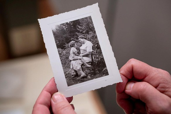 Photograph of hands holding a black and white photo of ballad singer Texas Gladden seated in a chair, outdoors, with one of her children sitting on her lap facing her.