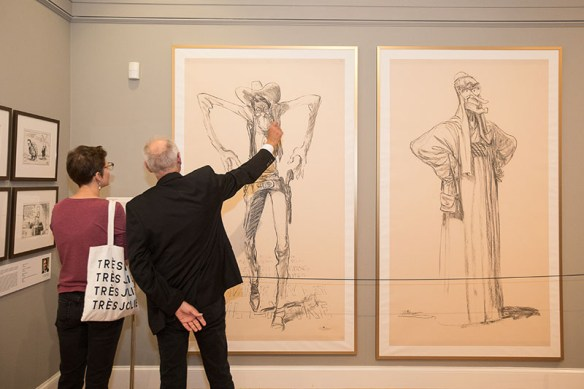 Viewers facing and discussing discussing a display of Oliphant's full-sized depiction of President Reagan as a Wild-West gunslinger with his hands poised over pistols in his holsters. To the right is another full-sized drawing of President George H. W. Bush, hands-on-hips, robed head-to-toe in Arab dress.