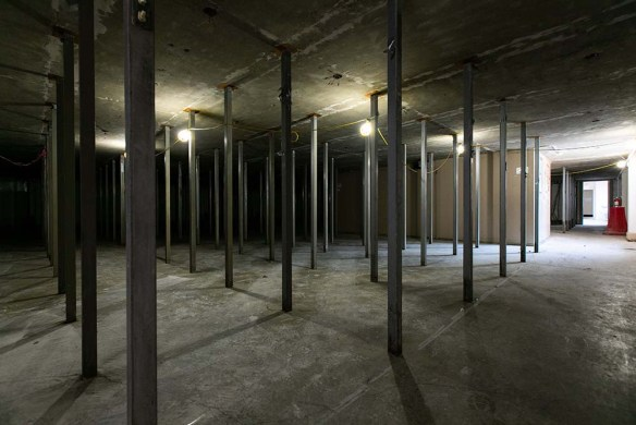 A concrete floor and ceiling with regular poles arranged vertically.