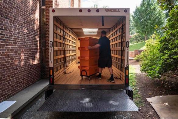 Worker inside a van, pushing a dolly stacked trays filled with books being moved out of the main library.