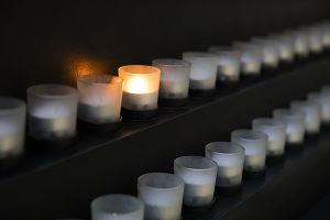 A votive candle burns alongside many other unlit candles