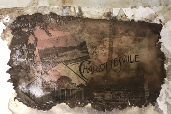 """Photo shows soggy, dirty and ragged paper sheet with images of Charlottesville. Word """"Charlottesville"""" is clearly visible."""