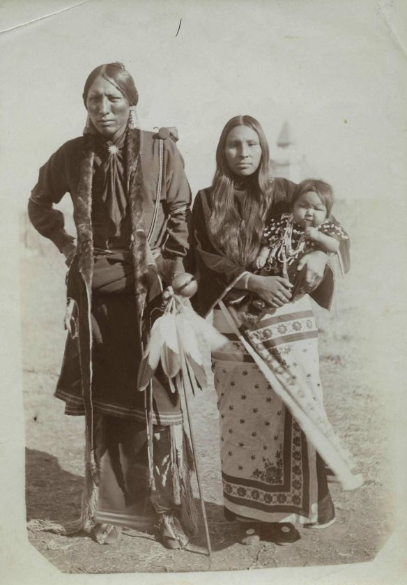 Man and woman in indigenous clothing. Woman holds a baby, all three look directly toward the camera.