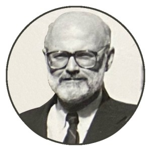 Circular cropped monchrome photo of a balding man with glasses and a beard, wearing a white shirt and dark suit and tie.