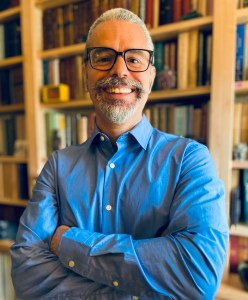 Photo of Bradley Daigle, with goatee and glasses, smiling, wearing blue collared shirt and standing in front of shelves of books