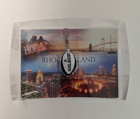 The fully-assembled final piece. The postcard sits in the clear box, and the insert sits on top of the postcard and provides support to the keychain, without allowing the keychain to rub against the card directly