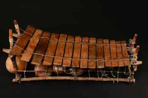 Photo of gyil instrument: a set of rectangular, vertical, wooden blocks, decreasing in size from left to right,.