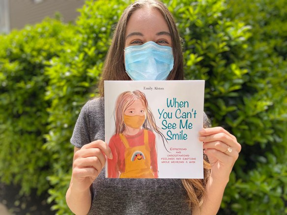 """Photograph of Ashley Hosbach, outdoors, wearing a face covering from nose to chin, and holding up a book, the cover illustrated with the picture of a young girl wearing a face mask. The title is """"When You Can't See Me Smile."""""""