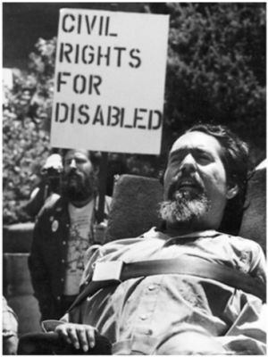 """Photo of Ed Roberts at a protest rally, viewed from the chest up, a seat belt across his chest secures him in his wheelchair. Behind him a protestor stands with a sign that says in all-caps """"CIVIL RIGHTS FOR DISABLED""""."""