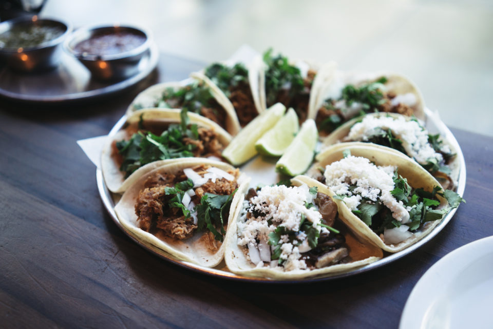 a plate of tacos with limes and cheese