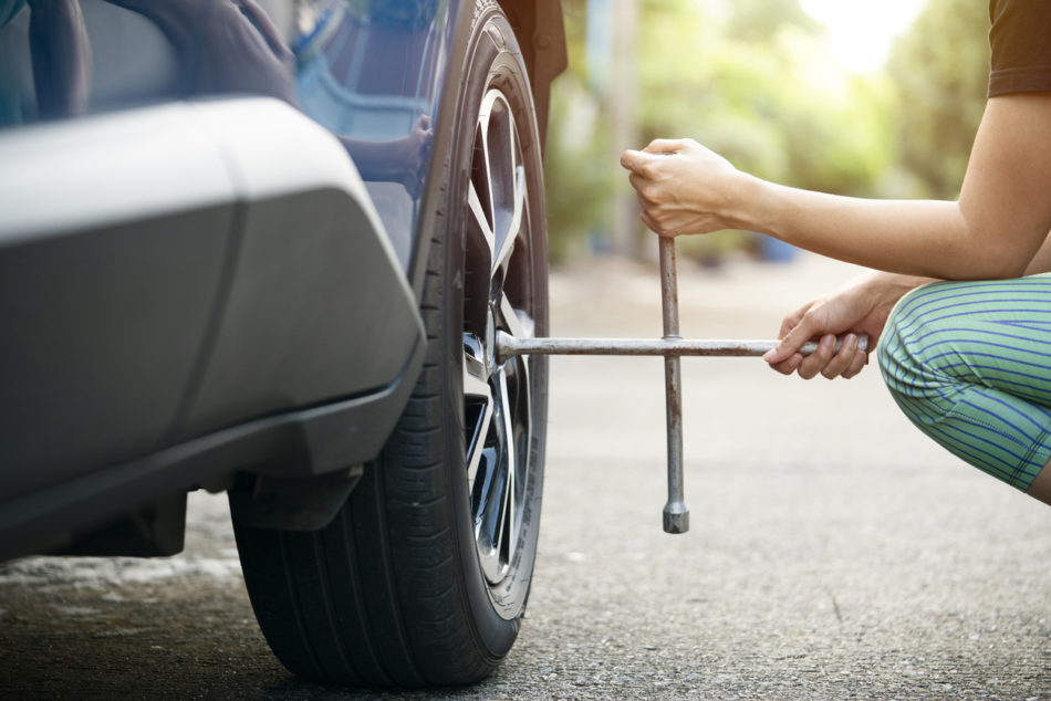 Woman changing tire on side of the road