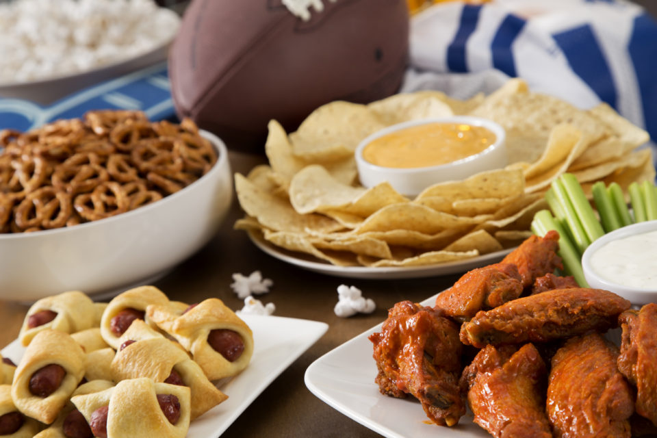 Tailgate party spread with hot wings, pig in a blanket, nachos, pretzels, and popcorn with football and a football jersey.