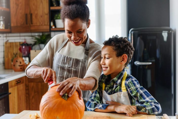 Mother and son carving pumpkin for Halloween holiday