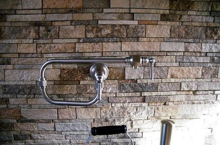 Stone backsplashes make an excellent backdrop to metal plumbing fixtures. (Image via Charlotte Granite Countertops on Flickr).
