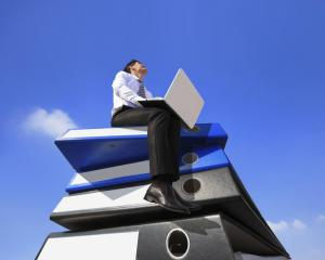 Happy business man using notebook computer and sitting on lots piles of document folders, technology concept