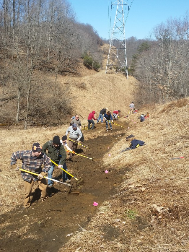 People working outdoors maintaining park trail