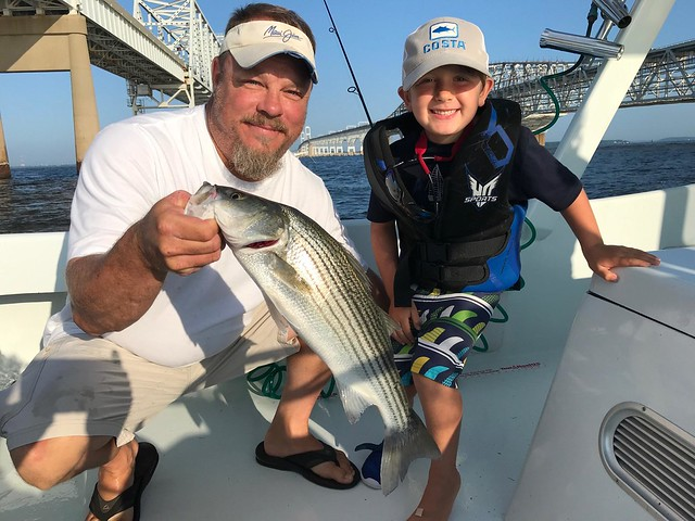 Photo of man and boy with striped bass