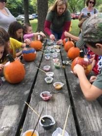 Photo of kids painting pumpkins