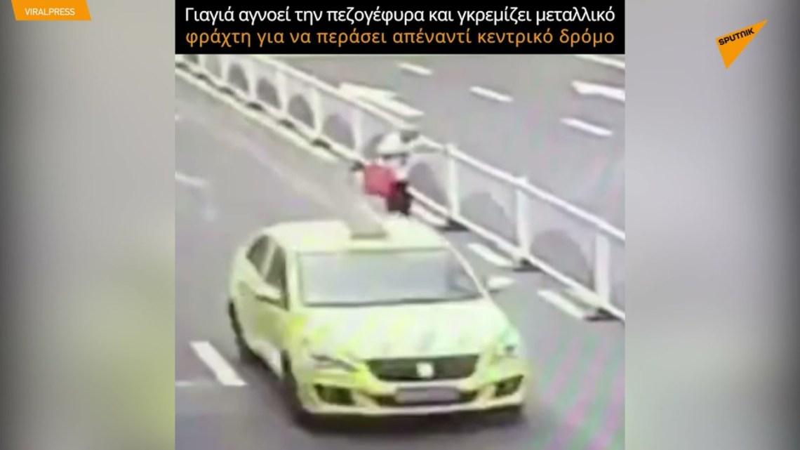 Γιαγιά αγνοεί την πεζογέφυρα και γκρεμίζει μεταλλικό φράχτη για να περάσει απέναντί κεντρικό δρόμο