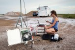 University of Oklahoma graduate student Liz Smith assembles a mobile weather station outside of the trailer for the Collaborative Lower Atmospheric Mobile Profiling System (CLAMPS). The system is a joint project of the University of Oklahoma and National Severe Storms Lab. This was one of the many mobile weather units gathering data duirng the PECAN project, a summer research project to better predict how severe storms form over the Great Plains.