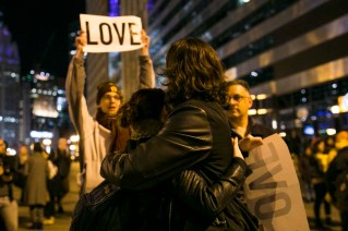 "Hugging in front of ""love"" sign"
