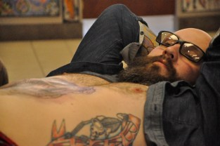 A patron leans back at Deluxe Tattoo in Uptown as he receives a chest piece from Los Angeles-based artist Jason Vaughn. This customer has dozens of tattoos, including a head piece. (Grace Austin/Medill)