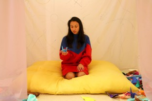 Artist Zitlali Yunuhem holds a paper crane in her hands in the Reiki-infused space, which is built for healing people's mind, body and spirit. Language symbols of victims can be found on fabrics of the tent. (Xiaozhang (Shaw) Wan/MEDILL)