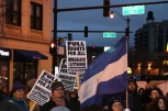 """Protesters hold signs that say """"Full rights for all immigrants! #LetThemIn!"""" as a Honduran flag flies. (Becky Dernbach/MEDILL)"""