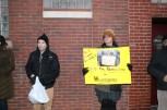 Outside a Pilsen art gallery, a protester holds a handmade sign. (Becky Dernbach/MEDILL)