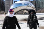 Two women bundled up against the cold stand in front of the Cloud Gate statue