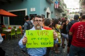 """A man holds a sign which reads in Spanish """"The UPR (University of Puerto Rico) is at risk of budget cuts"""" (Photo by Ankur Singh)"""