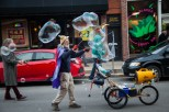 A man waving a bubble wand fills the air with abstract clouds. (Photo by Ankur Singh/Medill)