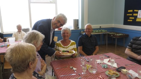Leader of the council, Cllr Stephen Alambritis, serving anniversary lunch to members of Friends in Lower Morden