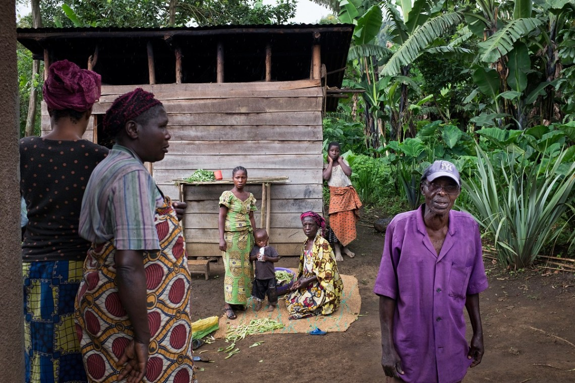 Retired charcoal burner Marcel Muhima with his relatives in front of his family home in Bushenge, North Kivu, DRC, November 2016. Photo by Leonora Baumann for Mongabay.