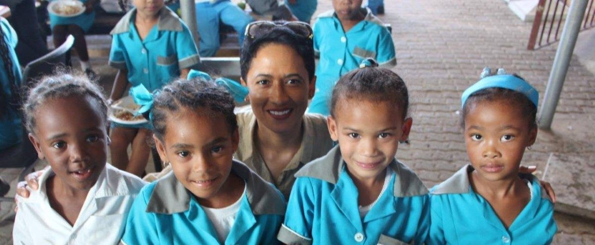 International woman winemaker Carmen Stevens with four school children who benefit from her school lunch charity