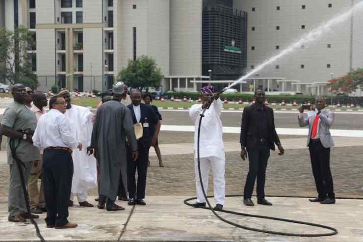 One of the Members of the National Assembly Tests the AFT Gun with others looking | Skytick AFT