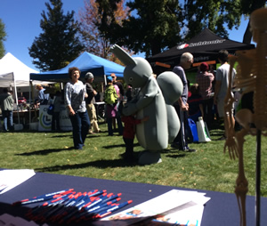 exhibitors view of the park with pens and brochures on the table and attendees and a person in a rabbit costume in the background