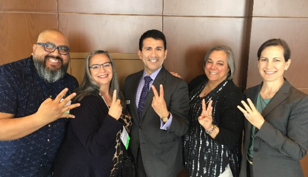 Knowledge River alumni holding fingers up signifying their cohort number