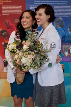 Two female students in white coats holding a bouquet of flowers smiling for the camera