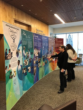 Two adult women looking at NLM traveling exhibit display