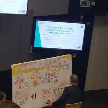 an illustrator drawing a whiteboard during a conference