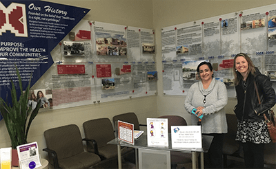 two women in front of a timeline of public health services in Nogales